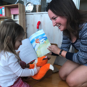A picture of a woman and a little girl reading Hey Rocco together