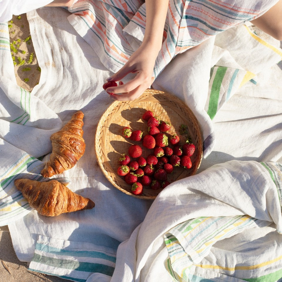 Picnic scene with Lapuan Kankurit textiles with bowl of raspberries and croissants