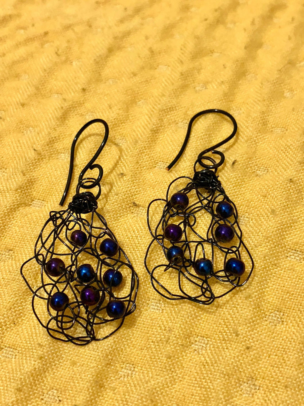 Handmade black wire crochet earrings with peacock blue pearls