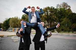 Groomsmen holding another groomsman up wearing gifts in New York