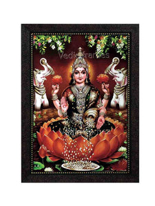Goddess Lakshmi on orange lotus in a lake with elephants on sides