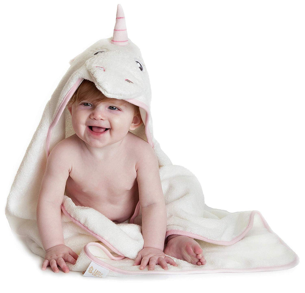 Alt = Baby sitting wearing Pink Unicorn hooded towel looking sideways