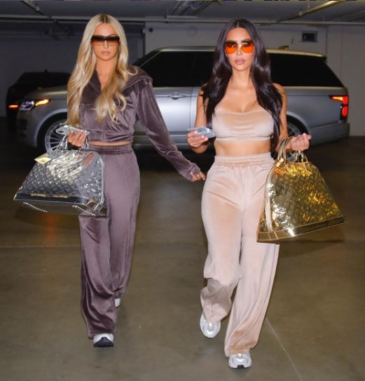 Paris Hilton and Kim Kardashian wearing SKIMS velour tracksuits.