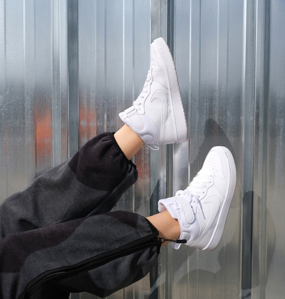 Person wearing white Nike Air Force sneakers.