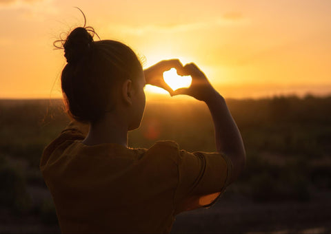 Woman making a heart silhouette at sunset