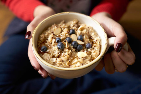 a cup of oatmeal with blueberries and pecans
