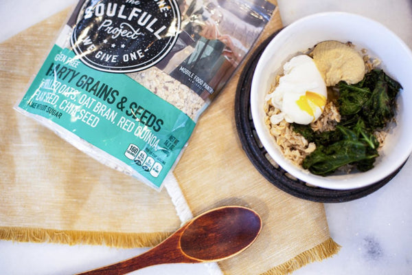 Bowl of Soulfull Hearty Grains & Seeds topped with eggs and spinach