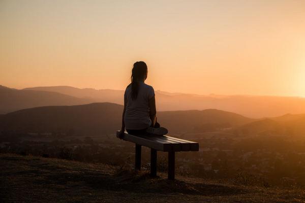 Woman sitting on bench during sunset at the top of a hike