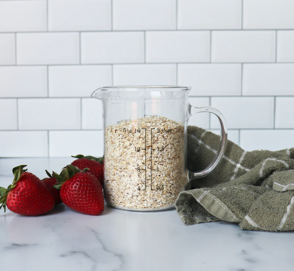 A measuring cup filled with whole grain oatmeal and strawberries on the side