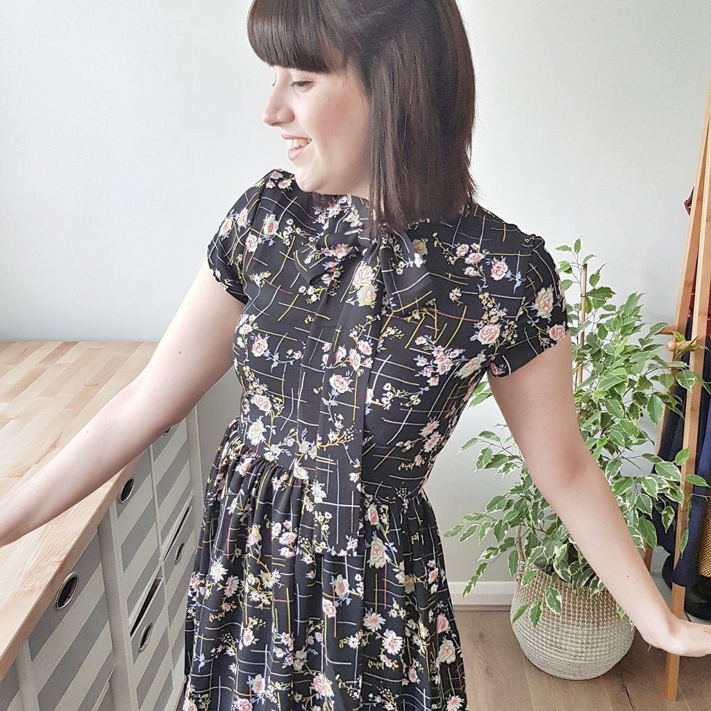1950s style retro black floral print tea dress with gathered full skirt and pussy bow neck tie flower print vintage-inspired outfit