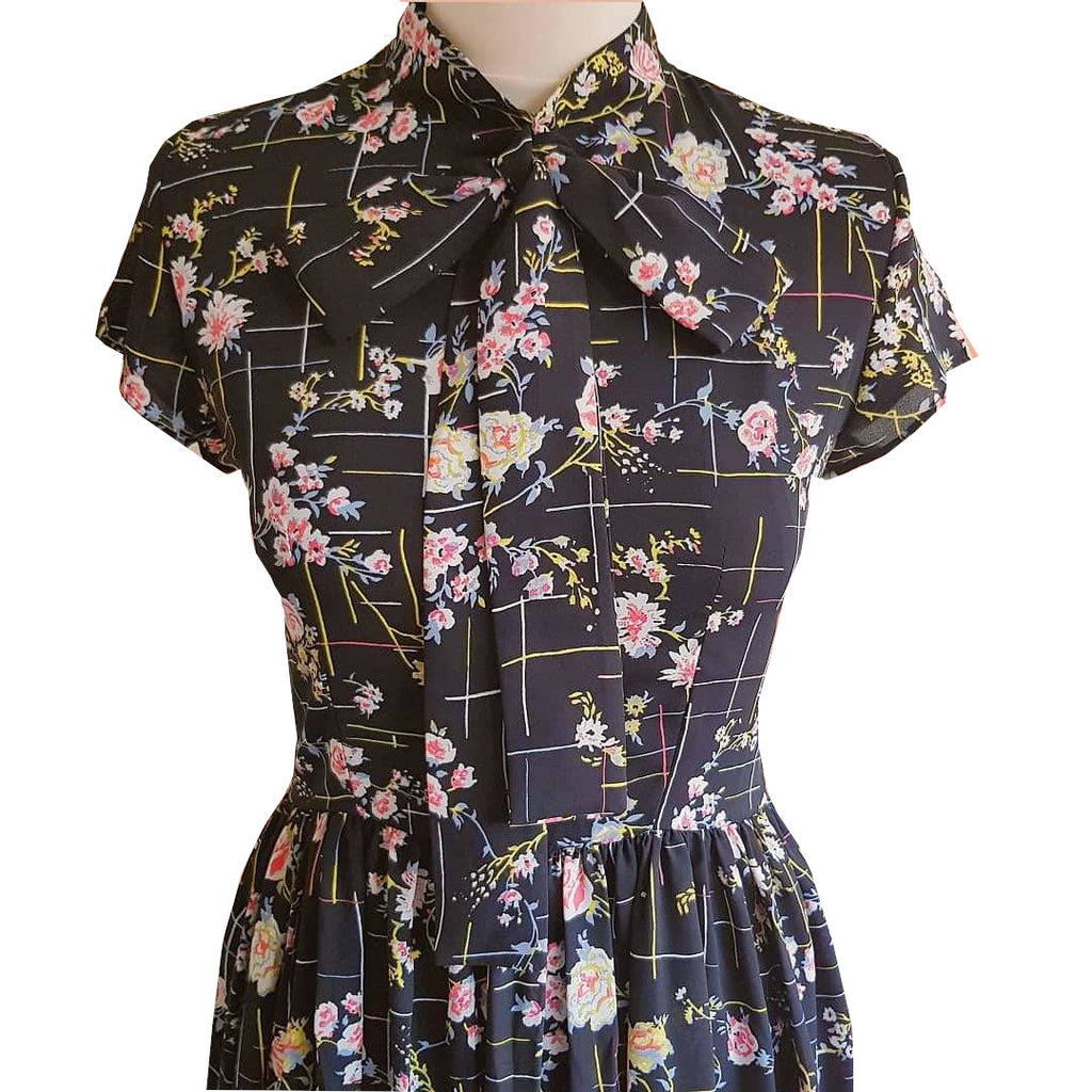 1950s style retro black floral print tea dress with gathered full skirt and pussy bow neck tie flower print vintage-inspired outfit handmade sustainable