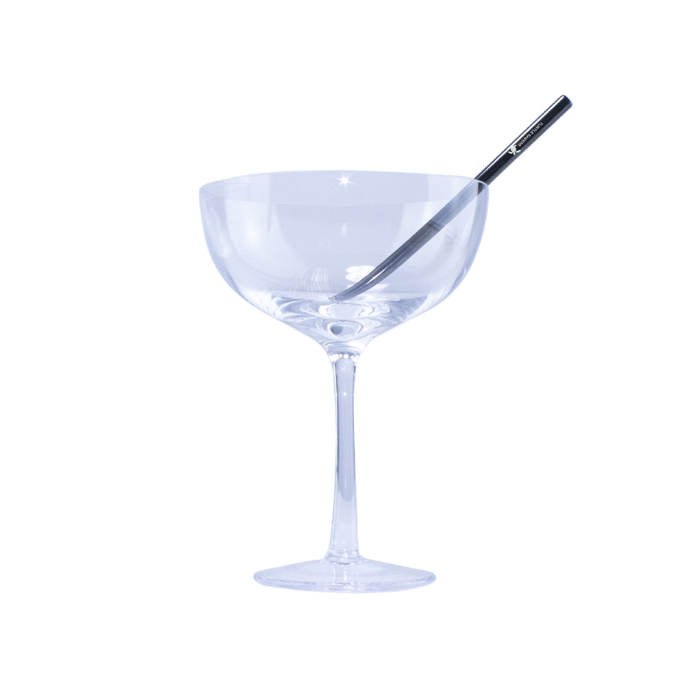 A picture of a cocktail glass with a black metal sip straw on a white background