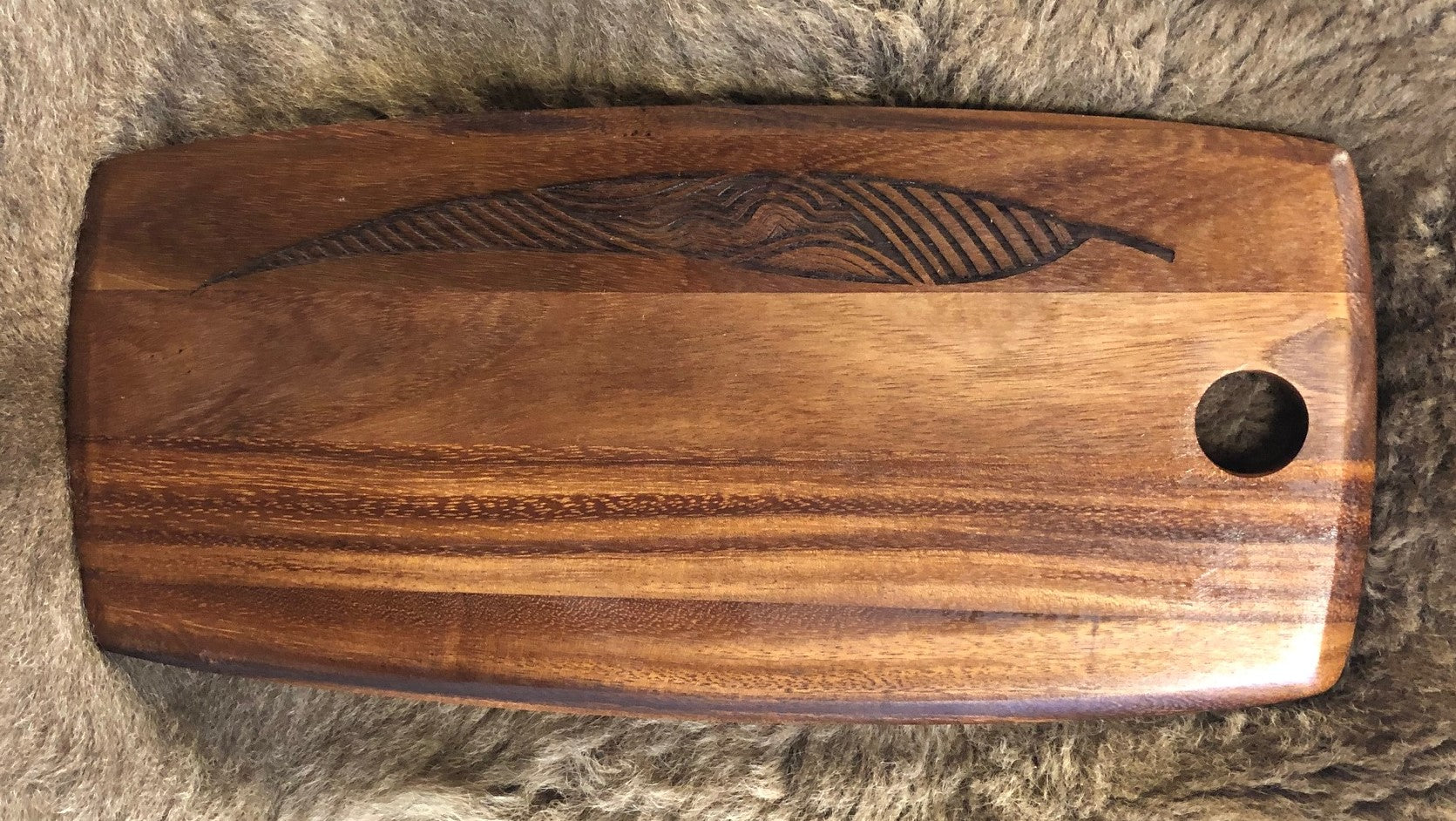 Acacia Wood Platter Small - Gum Leaves River Design   Each board has its own distinct pattern and is embellished with a Gum Leaf Design by Ngarga Warendj - Dancing Wombat - based on the Traditional symbols of South Eastern Aboriginal Art.  Your board comes with a card that gives the story of the artist and design.   Our boards are perfect for a house warming gift or spoil yourself and bring art into your everyday.  Our acacia boards are made from timber sourced from plantation grown trees