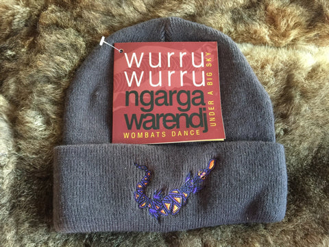 Ngarga Warendj Slate Grey Beanie with Embroidered Purple & Orange Bili the Blue Tongue Lizard Design   Bili the Bluetongue lizard eats all sorts of small creatures and only takes  what he needs.   Like Gaan the Snake, he is active after the cold time.