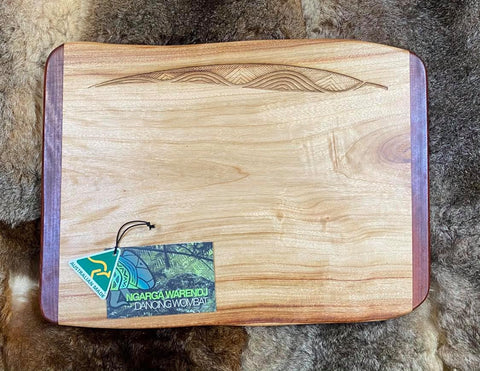 Camphor Laurel & Redgum Small Rectangle Board - Gum Leaves Mountains and Rivers Design by Ngarga Warendj - Dancing Wombat - based on the Traditional symbols of South Eastern Aboriginal Art. Your board comes with a card that gives the story of the artist and design. Use for a serving board for antipasto or cheese and biscuits or turn over and use the back for a cutting board and leave the side with the artwork lovely for your kitchen display. Antibacterial Properties & Environmentally Friendly