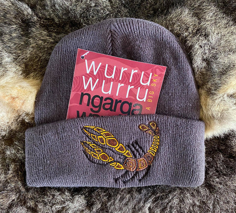 Ngarga Warendj Slate Grey Beanie with Embroidered Brown & Yellow Yabby Design   Bunggan Gulum the Yabby lives in wetlands, rivers, creeks, dams   and waterways. He builds his mud brick home for protection from   the elements and from predators.  He makes very good tucker   when boiled up.