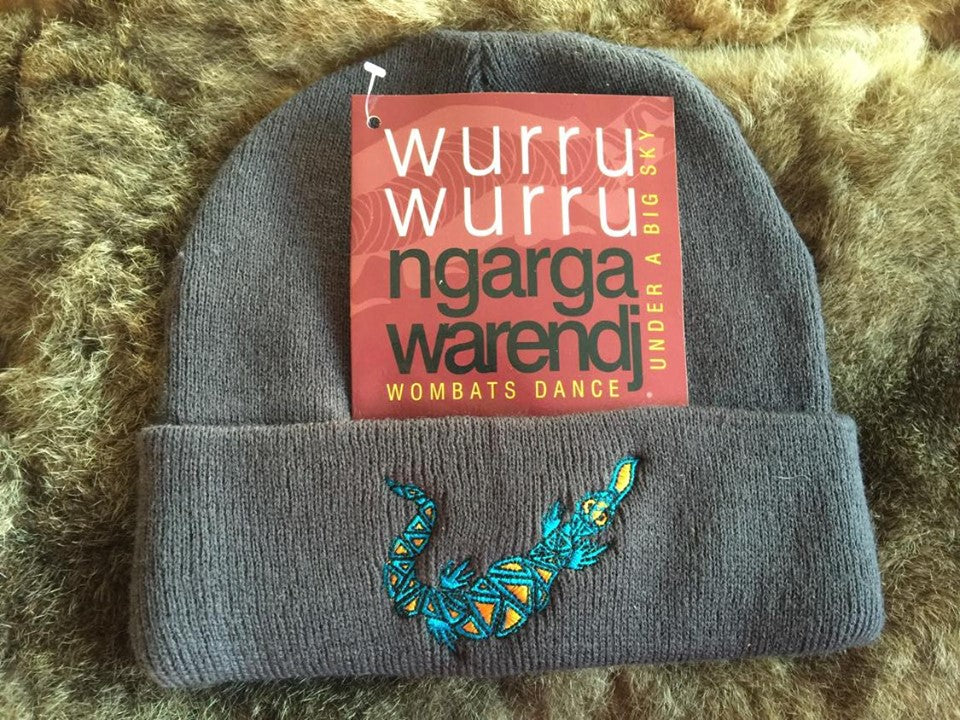 Ngarga Warendj Slate Grey Beanie with Embroidered Aqua & Orange Bili the Blue Tongue Lizard Design   Bili the Bluetongue lizard eats all sorts of small creatures and only takes  what he needs.   Like Gaan the Snake, he is active after the cold time.