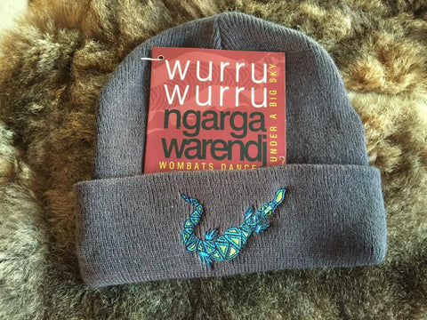 Ngarga Warendj Slate Grey Beanie with Embroidered Blue & Green Bili the Blue Tongue Lizard Design   Bili the Bluetongue lizard eats all sorts of small creatures and only takes  what he needs.   Like Gaan the Snake, he is active after the cold time.