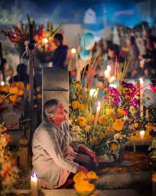 Elderly woman sits by a tomb, adorned with candles and flowers