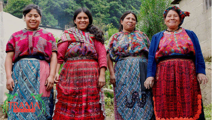 Group of smiling Mayan weavers, dressed in red and blue traditional huipil and corte, from an Indigenous Community of the Guatemalan Highlands