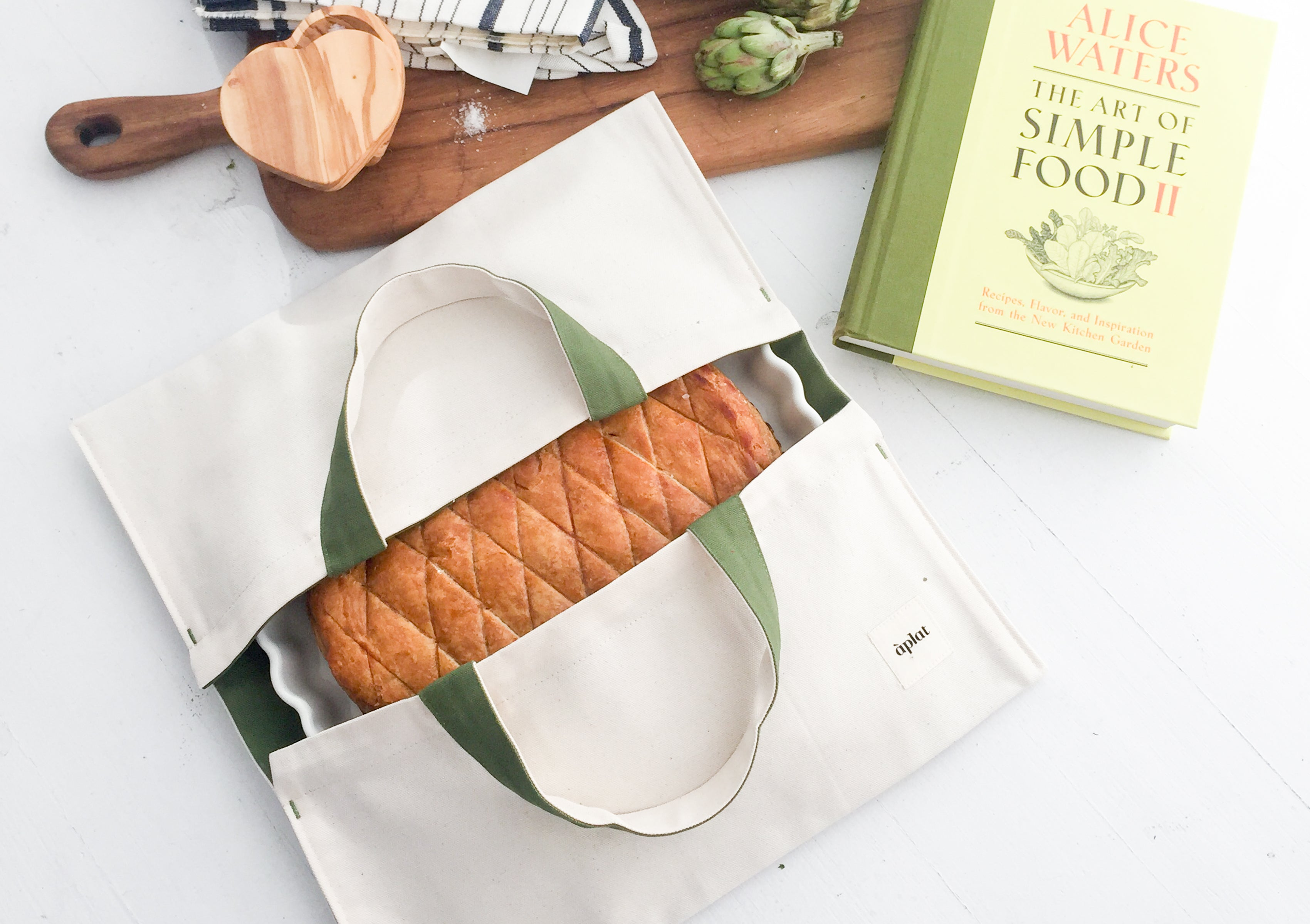 The Aplat Plat Wide Tote is designed to carry deliciously prepared food. Simply slide a plate or bowl through the center opening to keep items horizontal and upright. Perfect for potlucks, picnics and everyday shopping.