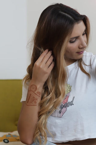Woman wearing Aphrodite henna design on her wrist