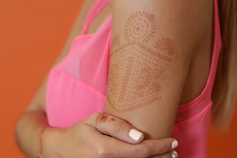 Woman with Aphrodite henna tattoo on her shoulder