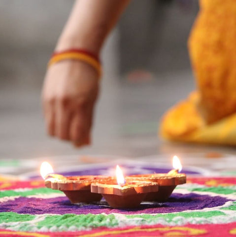 Creating a Rangoli for Diwali with Diya lights in the center