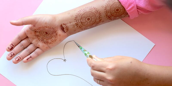 Girl practice henna tattoo designs on paper