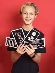 Boy holds up a selection of henna tattoo stencils
