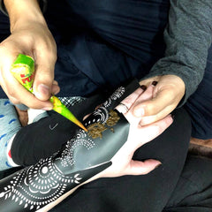 Apply henna paste onto henna stencil