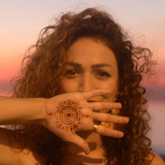 Woman with Camellia mandala henna tattoo on palm