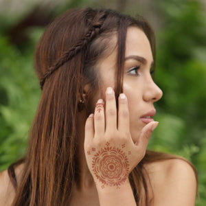 Blossom - woman with mandala henna tattoo on back of hand