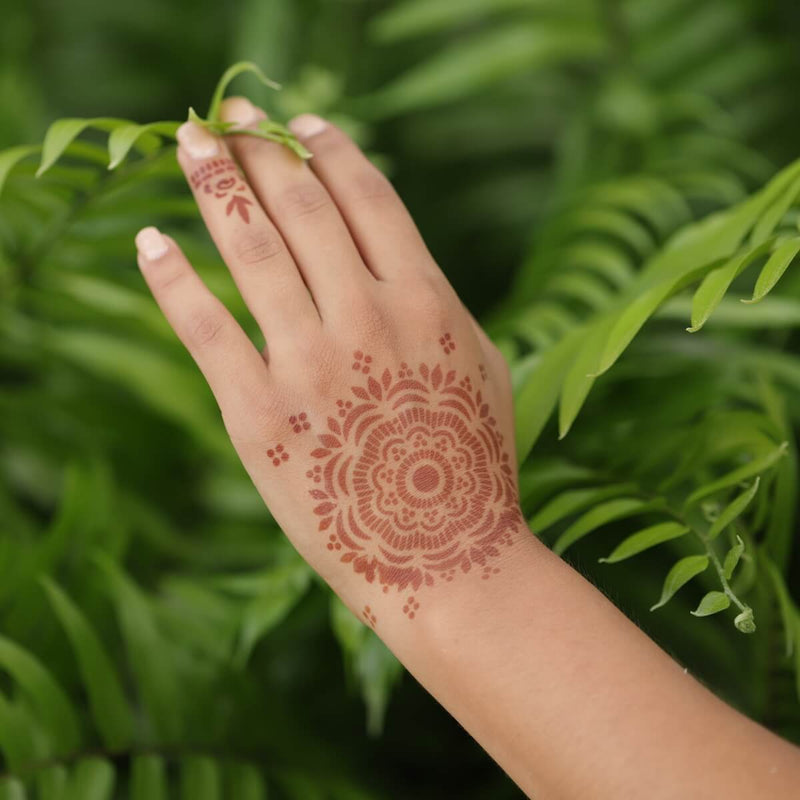 Brown Henna Tattoo on Back of Hand with Leafy Background