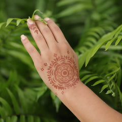 Woman wearing Mihenna's Blossom henna tattoo on back of hand