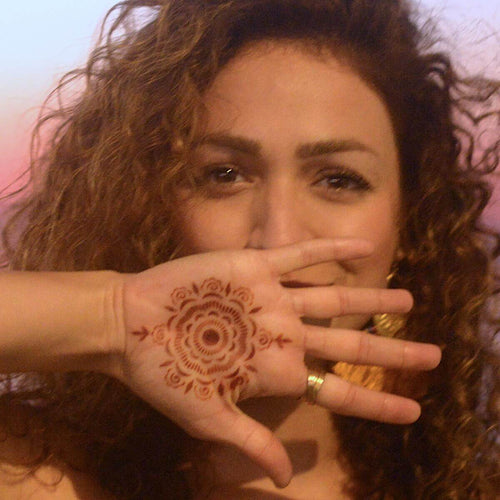 Camellia - Woman with mandala henna tattoo on palm
