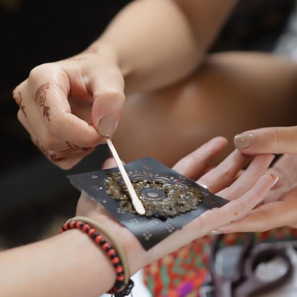 Applying henna paste to henna stencil on palm