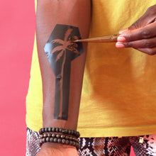 Load image into Gallery viewer, Palma - applying organic henna paste to a palm tree henna stencil on arm