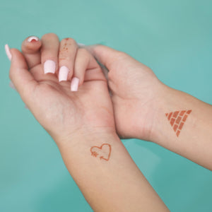 Sand - mini henna tattoos of heart and pyramid on wrists