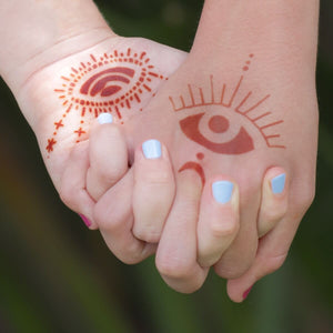 Starry Eyes - intricate eye henna tattoos on girls holding hands