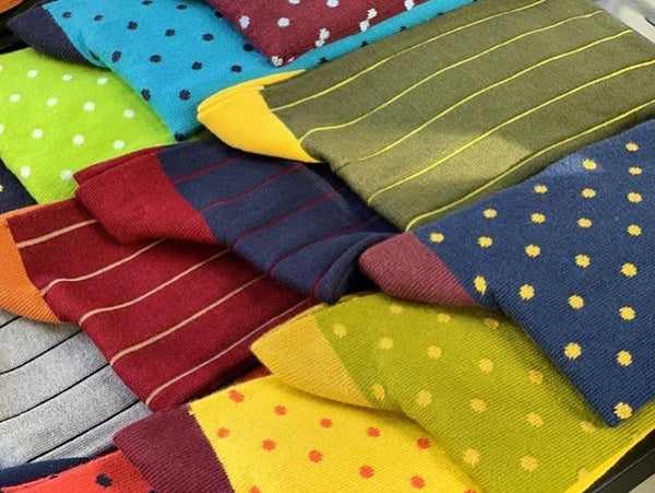 Many colourful Peper Harow socks with different patterns laid out