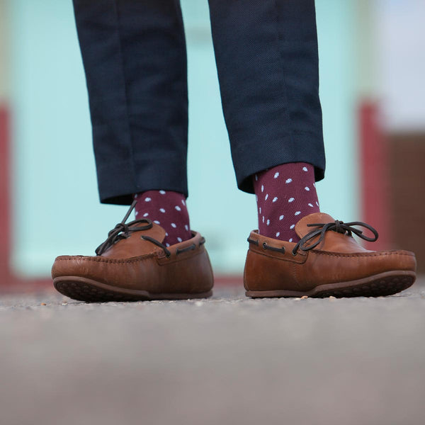 Man wearing navy trousers and brown shoes and Peper Harow burgundy pin polka socks