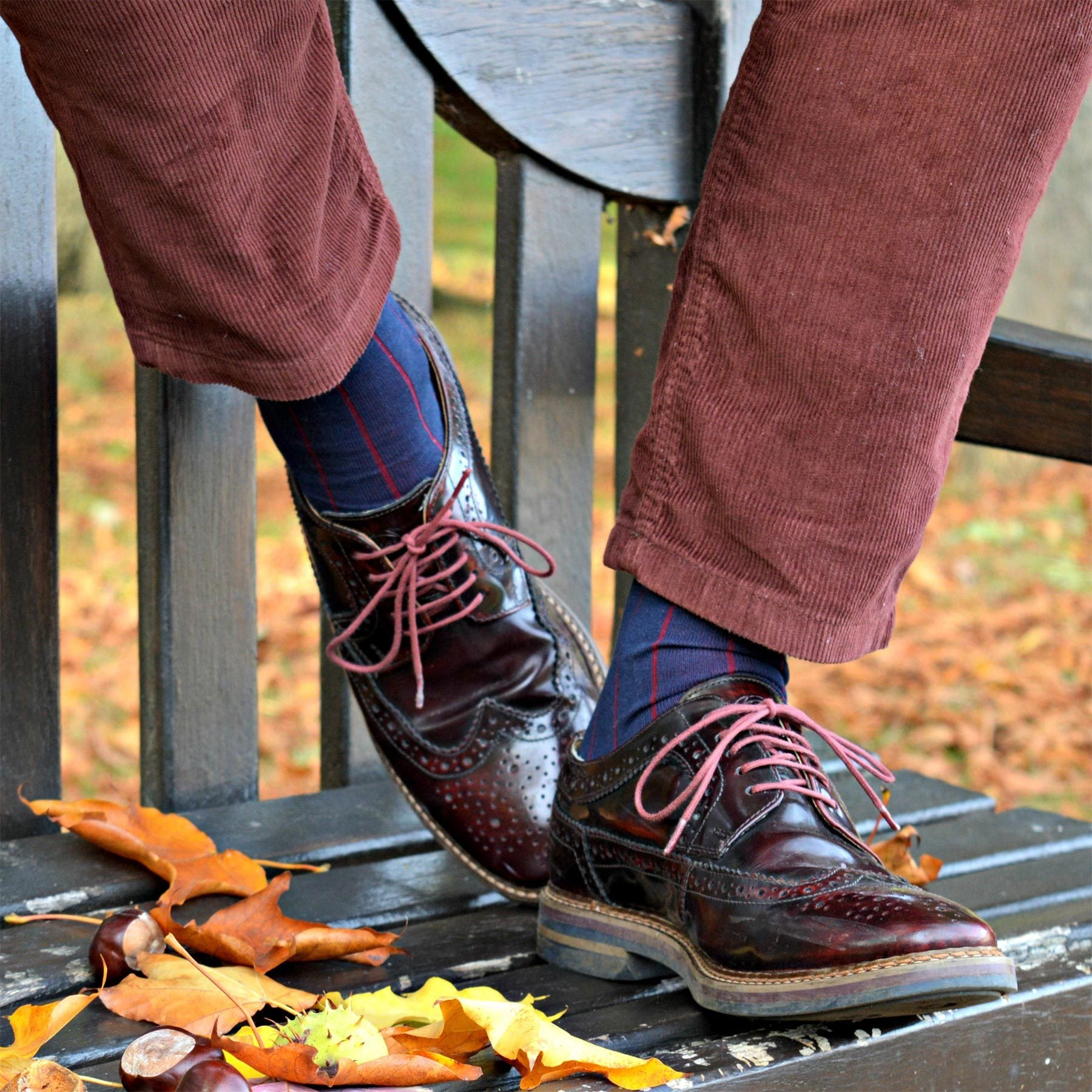 Man wearing corduroy trousers, smart shoes and Peper Harow Pin Stripe Men's socks standing on a bench in Autumn