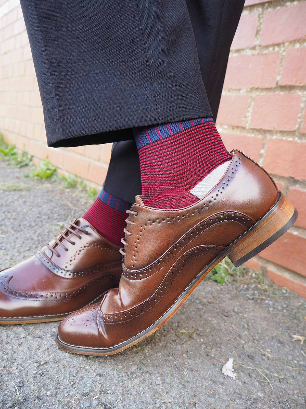 Man wearing smart trousers and brown brogues and Peper Harow Navy Oxford Stripe socks leaning against a wall