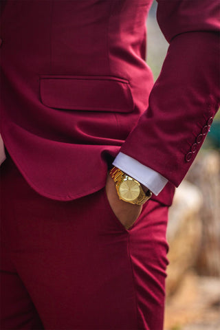 Man wearing stylish burgundy suit and gold watch