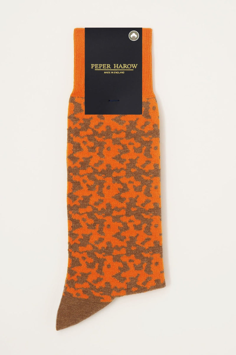 Maelstrom orange men's luxury socks by Peper Harow, featuring a quirky brown pattern and brown toe and heel in packaging.