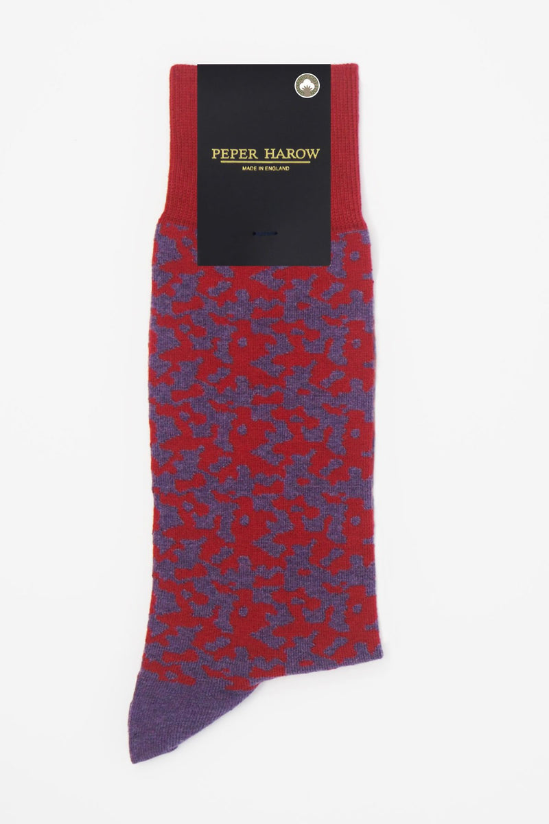 Maelstrom red men's luxury socks by Peper Harow, featuring a quirky purple pattern and purple toe and heel in packaging.