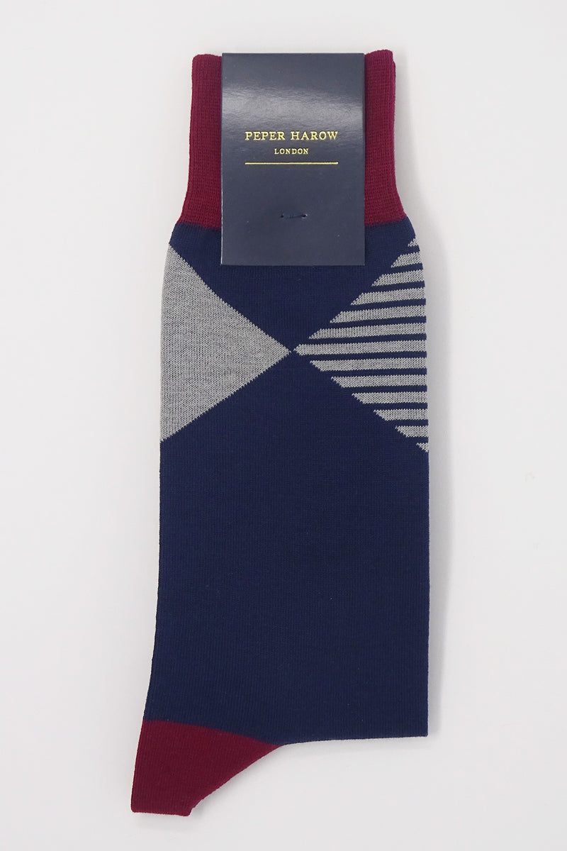 Navy socks with a red cuff, heel and toe, with a grey diamond shaped pattern around the ankle in packaging
