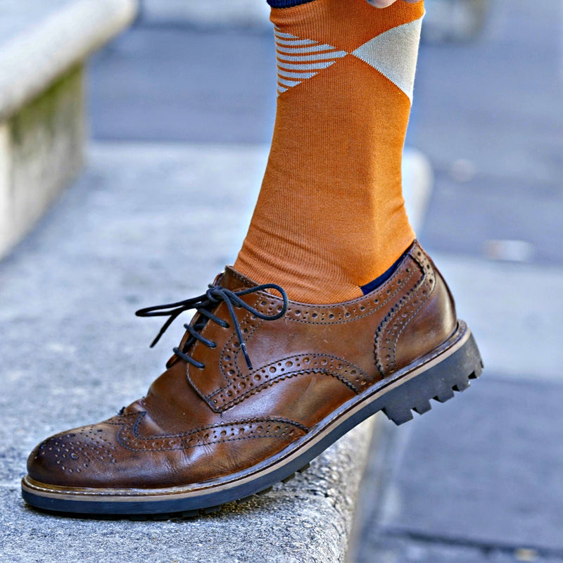 Man wearing leather oxford shoes, pulling up Orange Big Diamond socks.