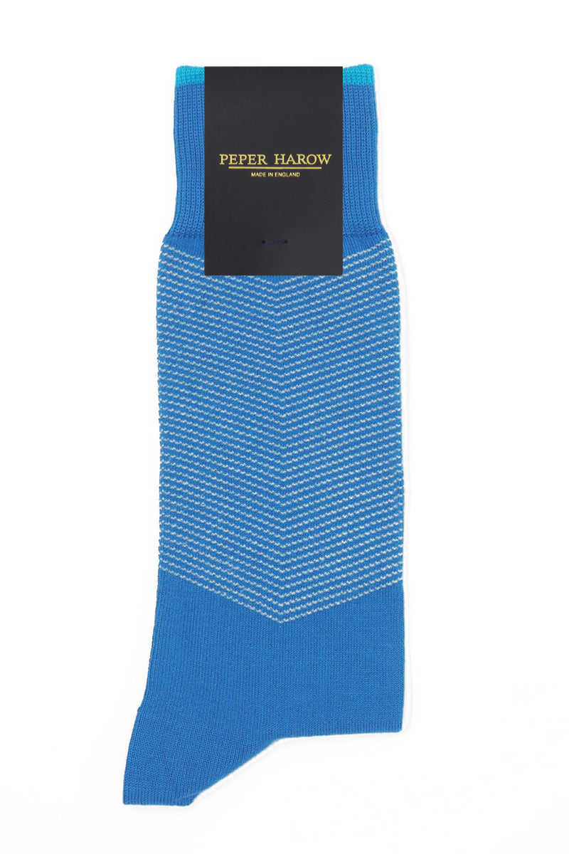 A pair of Sapphire blue men's chevron socks in packaging, with a white V striped pattern down the calf, and a turquoise line circling the top of the cuff